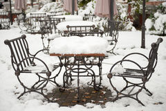 Metal table and chairs covered with snow Royalty Free Stock Photography