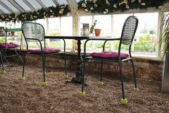 Metal Table and chairs in a garden centre coffee shop. Green painted metal table and chairs in a Sussex nursery coffee shop restaurant serving afternoon tea stock photo