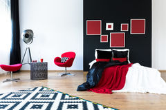 Spacious design bedroom. Metal table between comfortable red chair and pink stool in spacious design bedroom Stock Photo