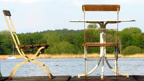 Metal table and two old chairs on wooden jetty stock video footage