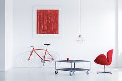 Metal table with wheels. Red glass standing on metal table with wheels in white room with poster Royalty Free Stock Images