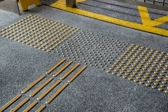 Metal tactile paving for blind people in big city Royalty Free Stock Image