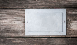 Metal tag on wood background Stock Photos