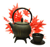 Metal tea pot with cup and maple leaves Stock Photo