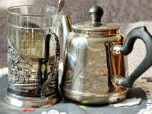 Metal Teapot and glass in cupholder. Glass holder appeared on the Russian railway in 1892. Retro. Metal Teapot and glass in cupholder. Glass holder appeared on stock photo