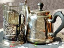 Metal Teapot and glass in cupholder. Glass holder appeared on the Russian railway in 1892. Retro. Metal Teapot and glass in cupholder. Glass holder appeared on royalty free stock photography