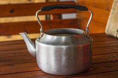 Metal teapot. On the wooden table royalty free stock photos