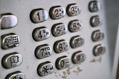 Metal telephone dial in the public phone booth with black letters and numbers on the silver plated buttons Stock Photos
