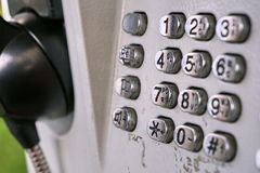 Metal telephone dial in the public phone booth with black letters and numbers on the silver plated buttons Royalty Free Stock Photo