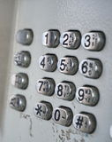 Metal telephone dial in the public phone booth with black letters and numbers on the silver plated buttons Stock Photo