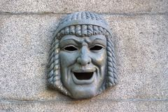 Metal theatrical mask symbolizes humor on the granite fence. Saint-Petersburg. royalty free stock photography