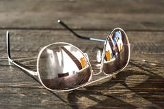 Free Metal Thin Trendy Sunglasses On Wooden Table. Outdoors Closeup. Royalty Free Stock Image - 106510526