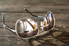 Metal thin trendy sunglasses on wooden table. Outdoors closeup. Stock Photography