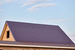 Metal tile on the roof of the house. The roof of the house is covered with burgundy metal tile royalty free stock photos