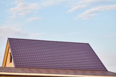 Metal tile on the roof of the house. The roof of the house is covered with burgundy metal tile stock photo