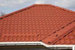 Metal tile roof. Red metal tile roof of a house against blue sky background royalty free stock image