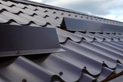 Metal tile roofing construction. Close up snow guard on the roof. Stock Photo