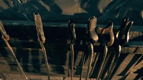 Metal tongs hanging on a rack at a forge. 4K stock footage