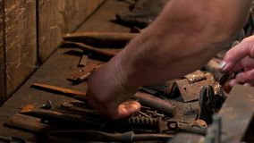 Metal tools of blacksmith are on the tabe. Blacksmith working with a rusty tools in a forge. Blacksmithing concept stock video