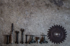 Metal tools, saw blade chisel wrench tap and drill bits laid flat on concre Stock Photography