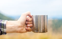 Metal touristic tea cup in man hand Royalty Free Stock Photo