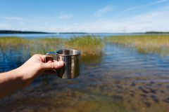 Metal touristic tea cup in man hand on outdoor background. Iron travel mug in hand from the first person on beautiful lake backgro. Und Stock Photo