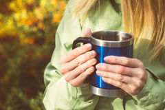 Metal touristic tea cup in Woman hands Outdoor. Lifestyle and Hiking concept with forest on background Stock Images