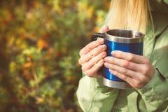 Metal touristic tea cup in Woman hands Outdoor Stock Image