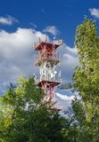 Metal tower with cellular repeaters installed on it for signal transmission. Against the background of trees, sky and clouds royalty free stock photo