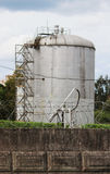 Metal tower with flammable fuel in the territory of a fence with barbed wire.  Stock Photography
