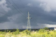 A metal tower of a high-voltage line of electrotransfers in the background of a stormy sky after a rain. Natural atmospheric pheno. Mena and modern technologies royalty free stock photo