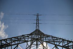 Metal tower for power lines in blue sky and sun with white clouds from under to see perspective. stock photo