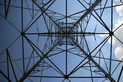 Metal tower for power lines in blue sky and sun with white clouds from under to see perspective. royalty free stock photos