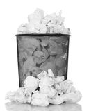 Metal trash can overflowing with paper waste isolated on white. Stock Photos