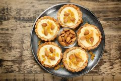 Metal tray with delicious crispy tarts. On wooden table Stock Photography