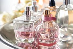 Metal tray with perfume bottles. On table stock photo