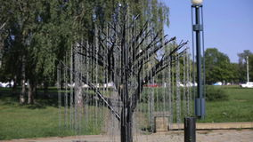 Metal tree in the park. Branches made of chains are swinging on the wind. Tradition hang lock for newlyweds stock video footage
