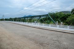 Metal Truss beam bridge with concrete road in countryside hill royalty free stock photos