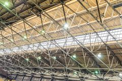 Metal trusses covering an industrial long-span building with an antiaircraft lantern. Of natural light Stock Photos