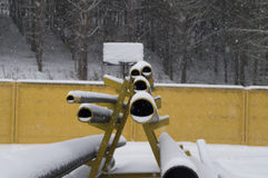 Metal tubes on racks stored outdoors in winter. Photo on the metal pipes of different diameters on the racks Royalty Free Stock Photography