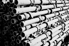 Metal tubes stack piled together scaffolding ledger members. In black and white mono monochromatic photography and this image is dynamic in light and shadows Royalty Free Stock Photo