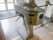 Metal turnstile at the entrance of an office. Turnstile is a mechanical gate with revolving horizontal arms allowing only one person at a time to pass through stock images