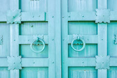 Metal turquoise aged textured door with rings door handles and metal details in form of stylized flowers. Stock Images