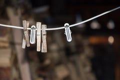 Metal velho e pregadores de roupa de madeira em uma corda Borrão do fundo fotos de stock royalty free