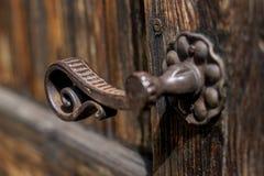 Metal velho - ferro, punho em uma porta de madeira fotos de stock