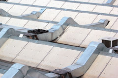 Metal ventilation ducts and tubes on a rooftop. Stock Images