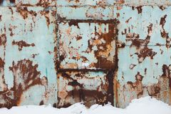 The metal wall of blue shade is rusty with time and weather conditions. It is winter outside and there is a lot of white snow on the ground royalty free stock photography