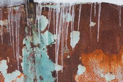 The metal wall of blue shade is rusty with time and weather conditions. It is winter outside and icicles hang from the roof stock photo