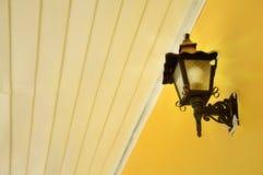 Metal wall lamp on yellow wall. The metal wall lamp on yellow wall Stock Images