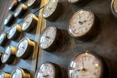 Metal wall with old styled clocks Stock Image